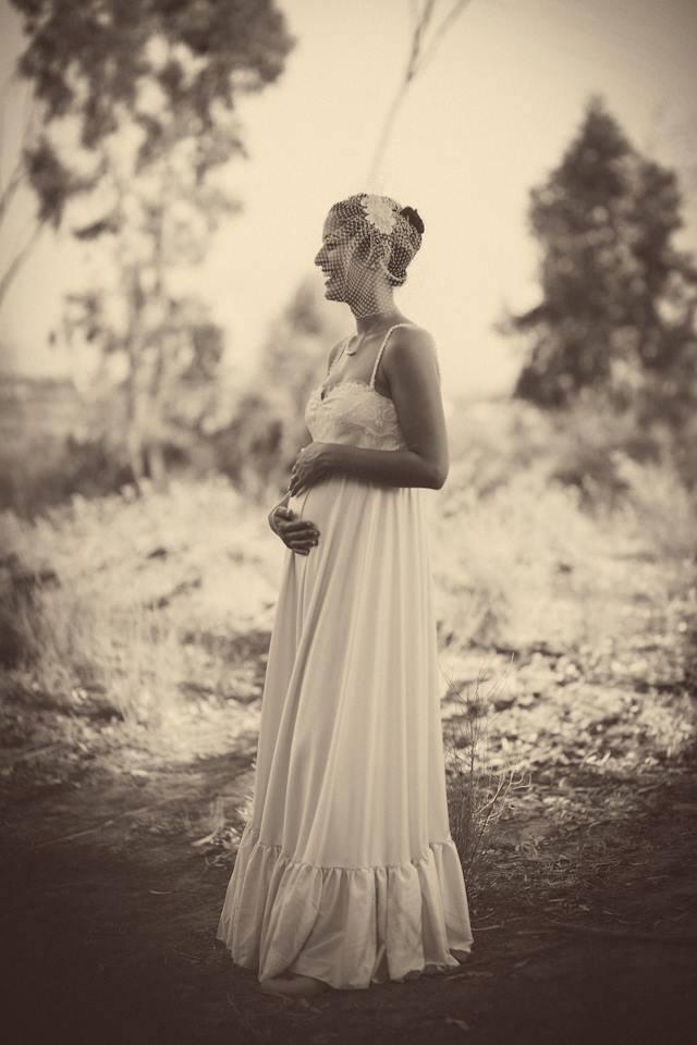 הילה בשמלת כלה לנשים בהריון מחזיקה באושר את פרי ביטנה